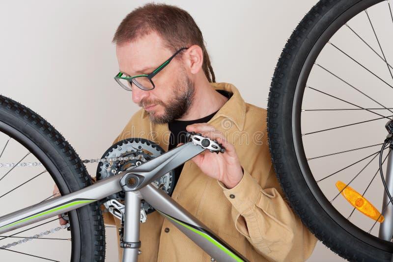 Bärtiger Mann überprüft die Befestigung des Hinterrads auf dem mtb b stockbild