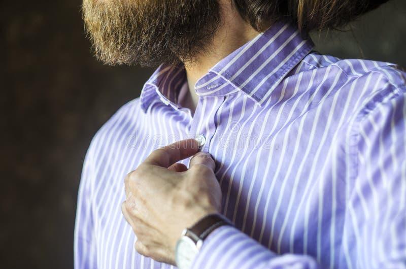 B?rtiger Mann in der Armbanduhr, die sein Hemd kn?pft stockbilder