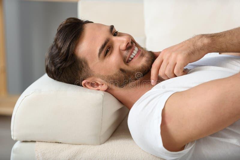 Bärtiger Mann, der auf einer Couch liegt lizenzfreie stockfotografie