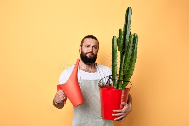 Bärtiger Mann, der eine Gießkanne und eine Blume nad die Kamera betrachtend hält lizenzfreie stockfotos