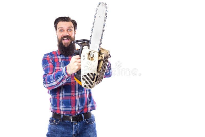 Bärtiger Mann, der eine Kettensäge lokalisiert auf einem weißen Hintergrund hält stockfotografie