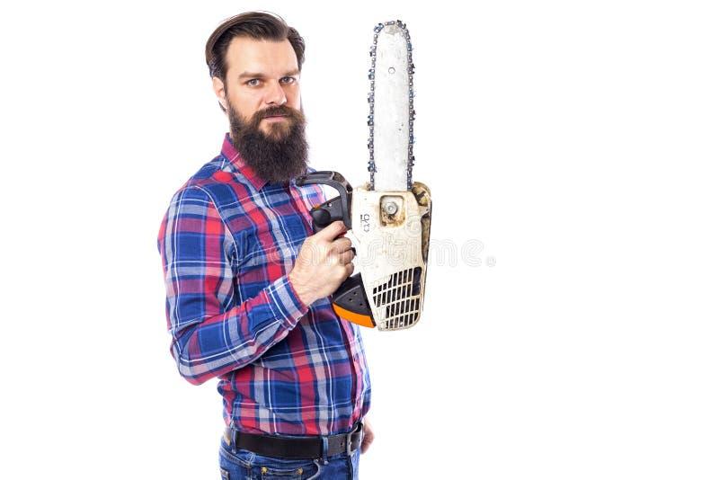 Bärtiger Mann, der eine Kettensäge lokalisiert auf einem weißen Hintergrund hält stockfotos