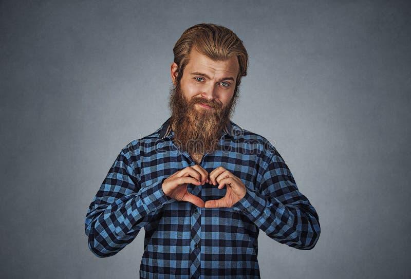 Bärtiger Mann, der Herzgeste mit den Fingern macht stockbild