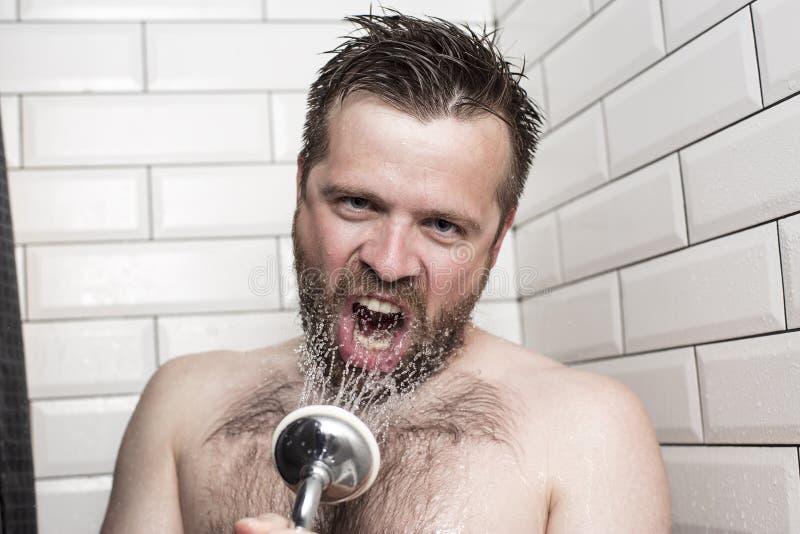 Bärtiger Mann, der im Badezimmer unter Verwendung des Duschkopfs mit f singt stockfoto