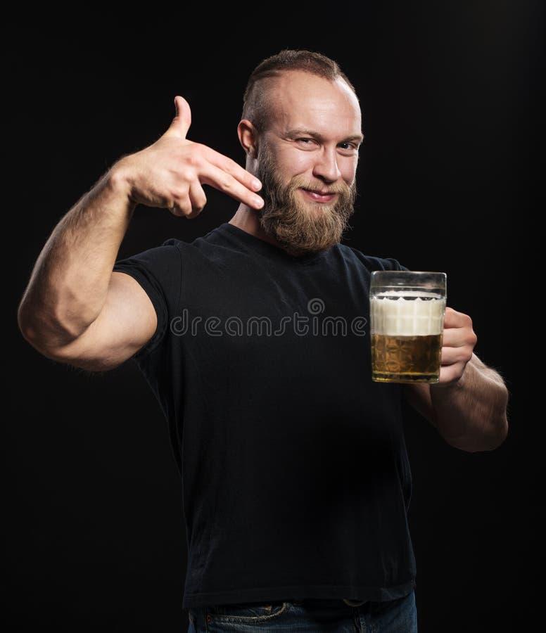 Bärtiger Mann, der mit einem Becher hellem Bier steht stockfoto