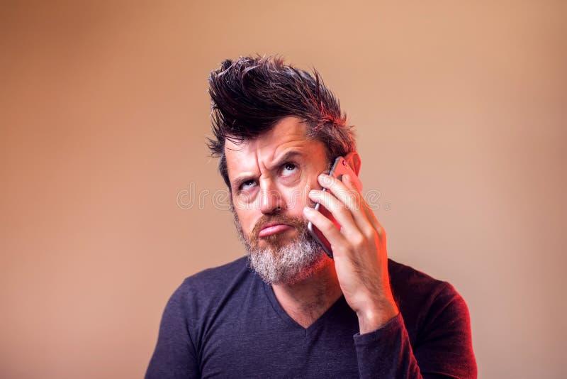 Bärtiger Mann, der oben beim Haben eines Schwätzchens an seinem intelligenten Telefon denkt und schaut Leute, Gef?hle, Technologi lizenzfreie stockbilder