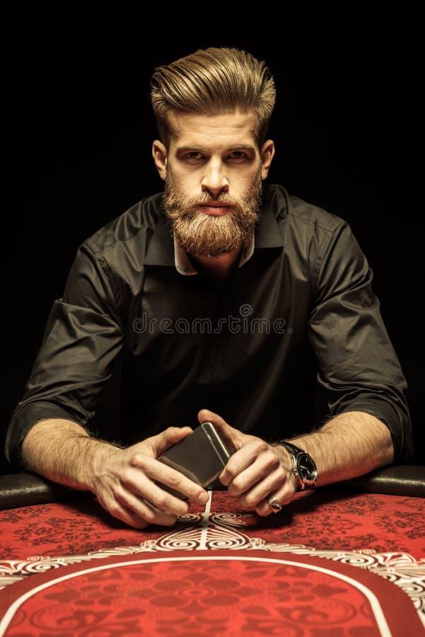 Bärtiger Mann, der am Pokertisch sitzt und Smartphone hält stockfoto
