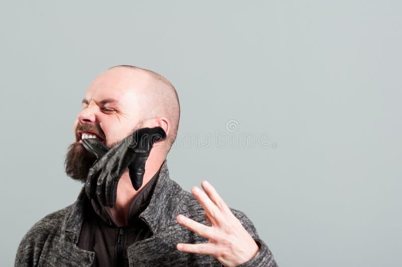 Bärtiger Mann, der seinen schwarzen Lederhandschuh mit den Zähnen auszieht lizenzfreie stockfotos