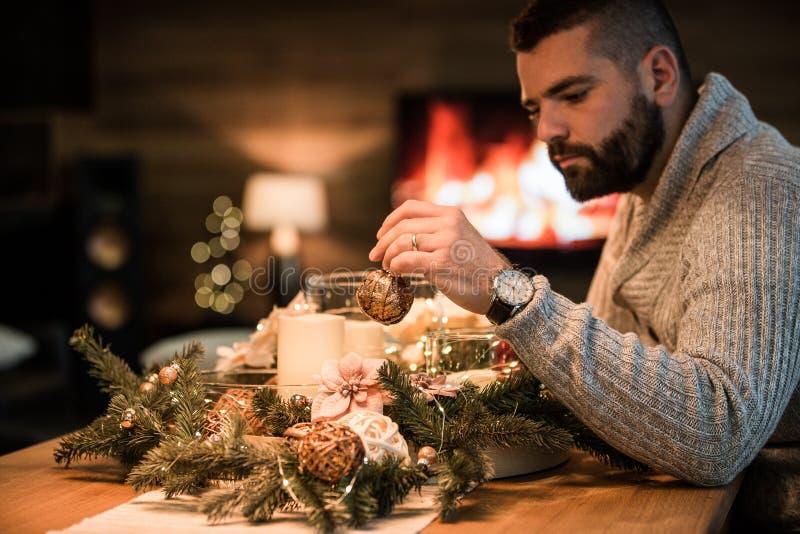 Bärtiger Mann, der Weihnachtstabelle verziert lizenzfreies stockbild