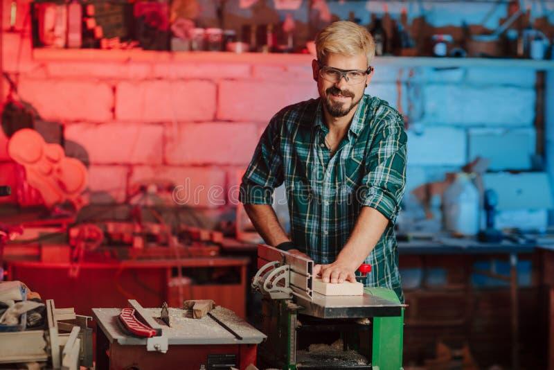 Bärtiger Mann des attraktiven jungen Hippies mit Augenschutzen durch Beruftischler-Erbauersägen mit Kreissäge a lizenzfreies stockfoto