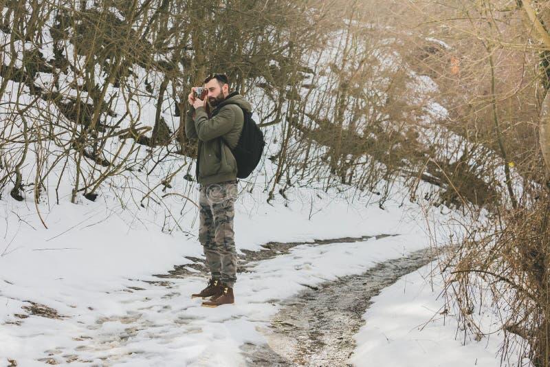 Bärtiger Mann des Hippies mit der Retro- Kamera, die in den Bergen Vorder steht lizenzfreies stockfoto
