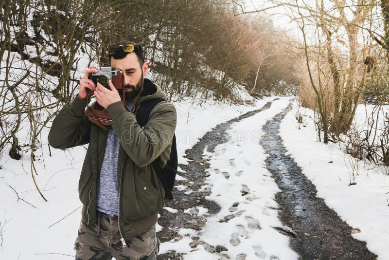 Bärtiger Mann des Hippies mit der Retro- Kamera, die in den Bergen Vorder steht stockfoto
