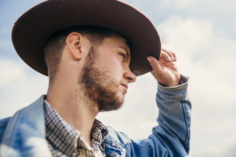 Bärtiger Mann des stilvollen Reisenden, der Hut auf sonniges mountai hält lizenzfreies stockbild