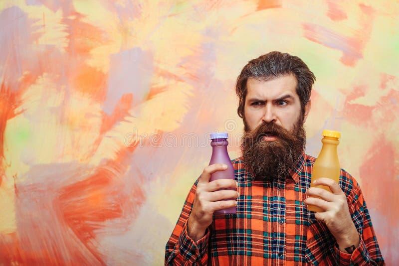 Bärtiger Mann des Stirnrunzelns, der zwei Plastikflaschen hält lizenzfreie stockfotografie