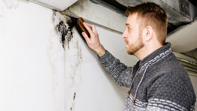 Bärtiger Mann entfernt schwarze Form auf der Wand nach Durchsickern stockbild