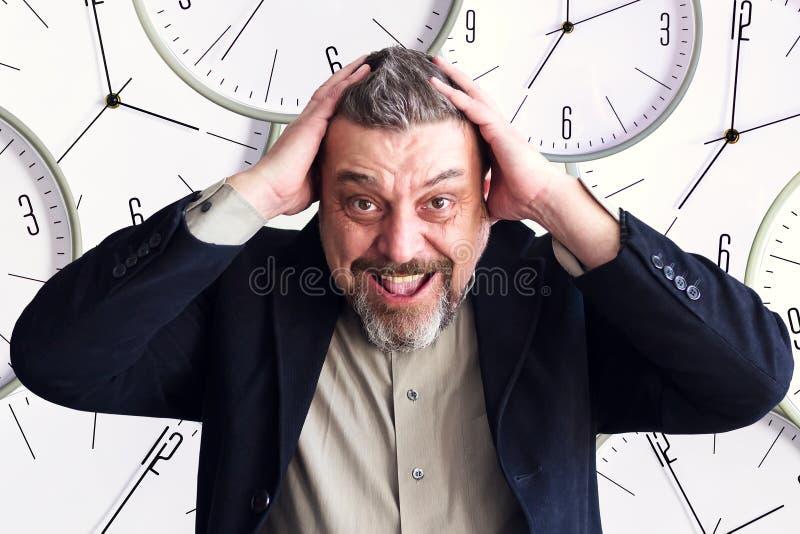 Bärtiger Mann hält seinen Kopf in beiden Händen Vor dem hintergrund der Uhr Zeitmangel Tätigen Sie nicht Geschäft lizenzfreie stockbilder