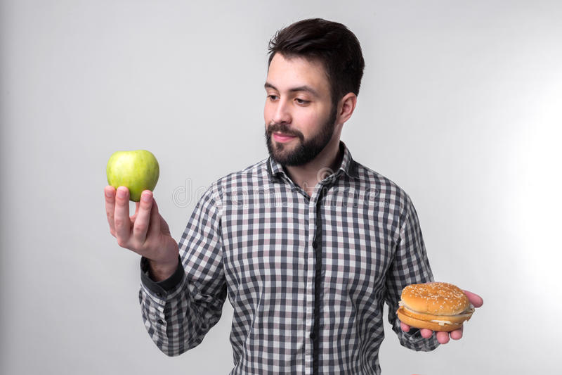 Bärtiger Mann im karierten Hemd auf einem hellen Hintergrund, der einen Hamburger und einen Apfel hält Kerl trifft die Wahl zwisc lizenzfreies stockfoto