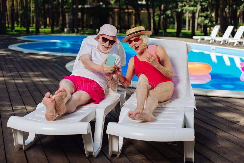 Bärtiger Mann im Ruhestand, der lustiges Video an seinem Telefon zeigt lizenzfreie stockbilder