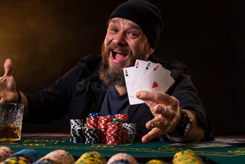 Bärtiger Mann mit der Zigarre und Glas, die am Pokertisch sitzt und Schreien lokalisiert auf Schwarzem stockfoto