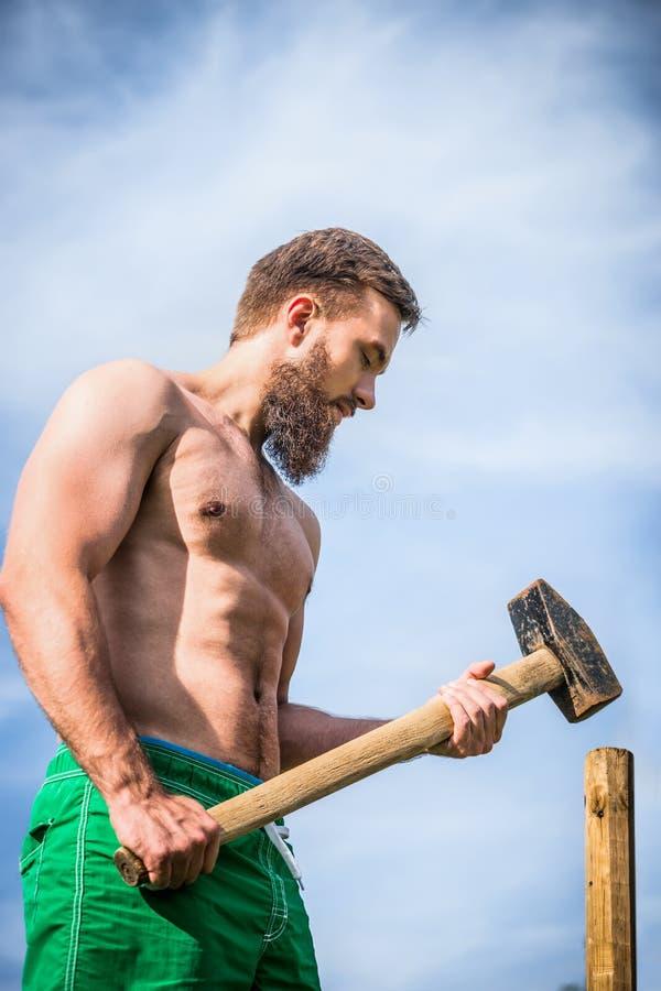 Bärtiger Mann mit einem nackten Torso mit einem Vorschlaghammer bearbeitet den Garten ein Hintergrund des blauen Himmels lizenzfreie stockfotos