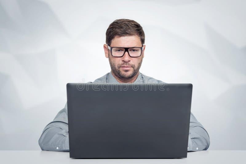 Bärtiger Mann mit Glasfunktion auf Laptop Blick auf den Schirm stockfoto