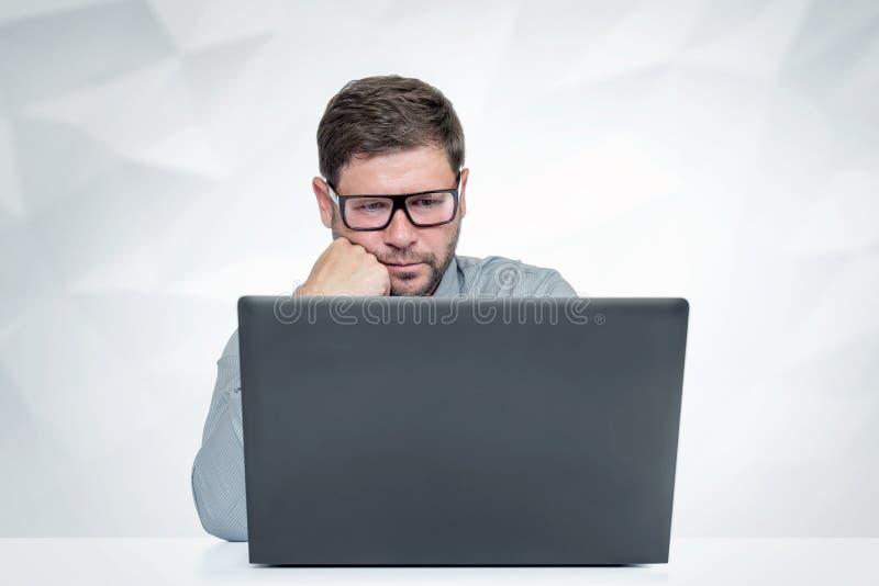 Bärtiger Mann mit Glasfunktion auf Laptop Blick auf den Schirm lizenzfreie stockfotos
