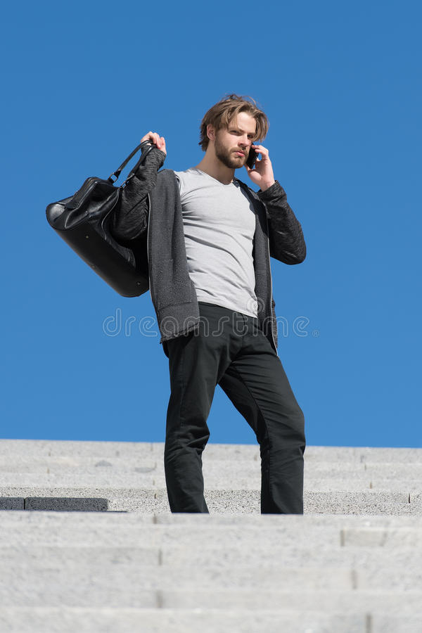 Bärtiger Mann mit Telefon und moderner Sport bauscht sich stockbild