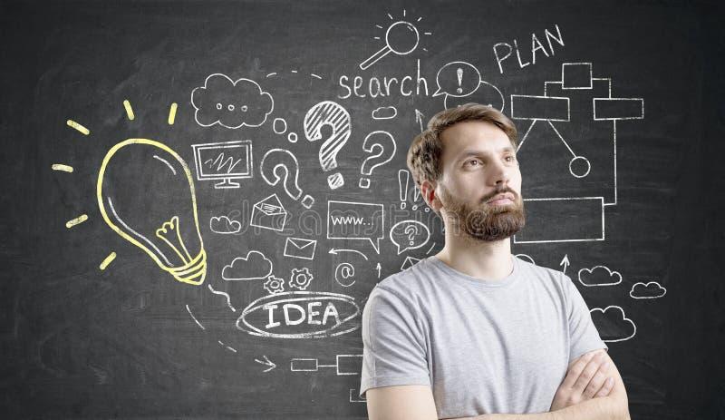 Bärtiger Mann nahe Geschäftsideenskizze auf Tafel stockbild