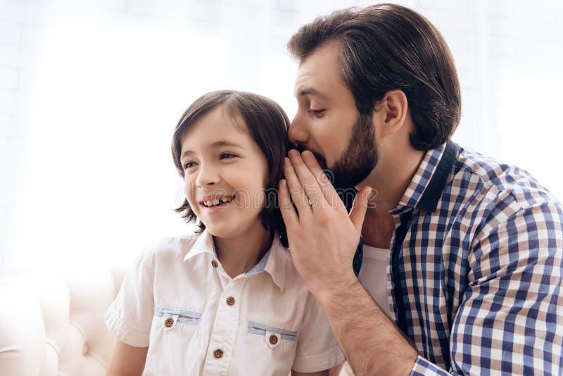 Bärtiger Mann sagt Geheimnis zum Ohr des Jugendlichen stockbild