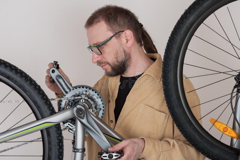 Bärtiger Mann schraubt die Pedale auf dem mtb Fahrrad stockbild