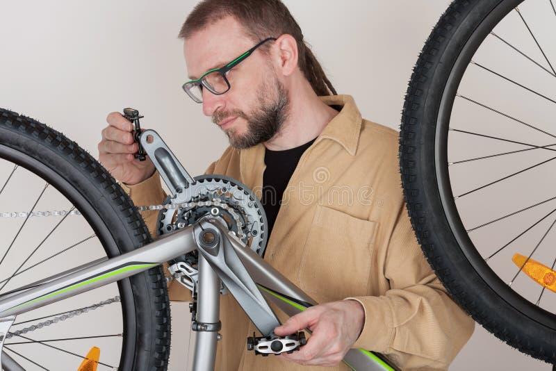 Bärtiger Mann schraubt die Pedale auf dem mtb Fahrrad lizenzfreies stockfoto