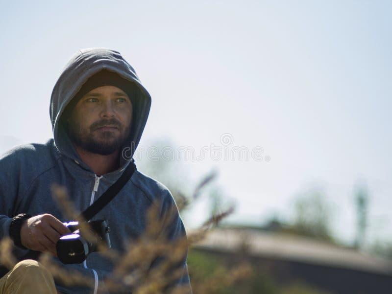 Bärtiger Mann sitzt gegen den Himmel und den Wald in der Haube und hält eine Kamera in seinen Händen lizenzfreie stockfotografie