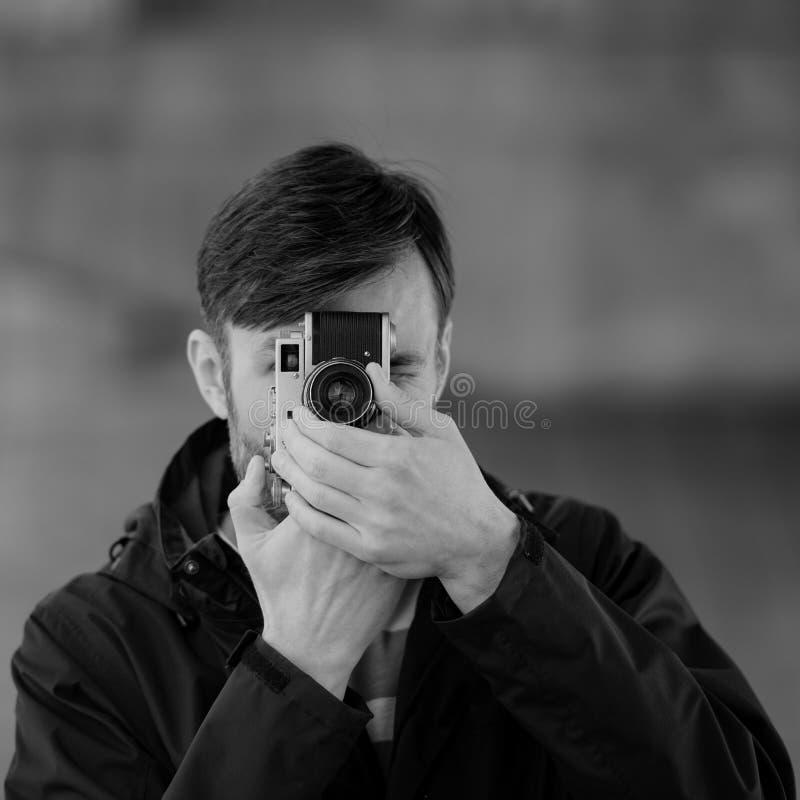Bärtiger Mannberufsfotograf passt auf und fotografiert wi stockbilder