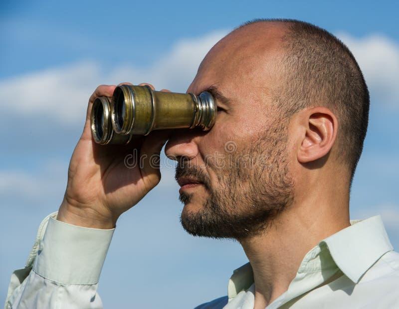 Bärtiger Manndetektiv schaut durch Ferngläser im Abstand a stockbild