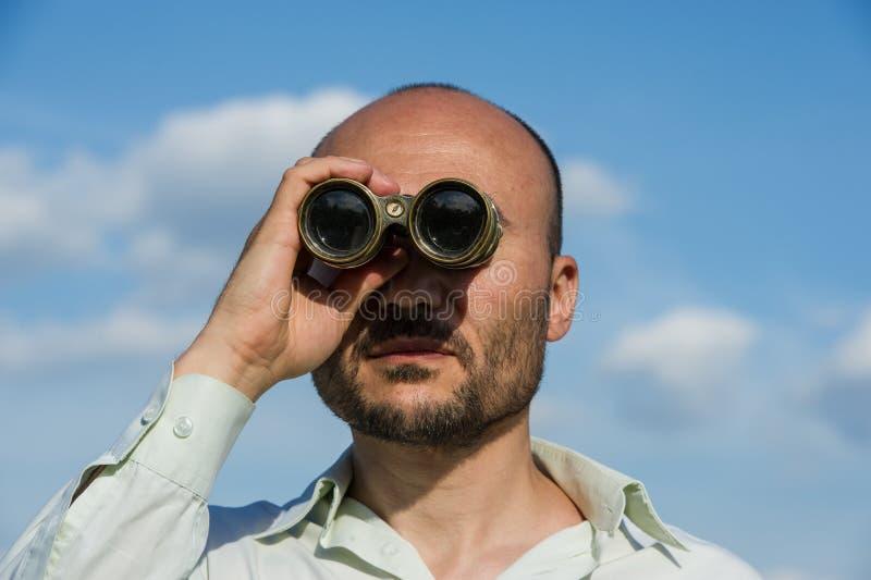 Bärtiger Manndetektiv schaut durch Ferngläser im Abstand a lizenzfreies stockfoto