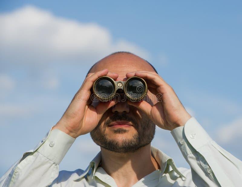 Bärtiger Manndetektiv schaut durch Ferngläser im Abstand a lizenzfreie stockfotografie