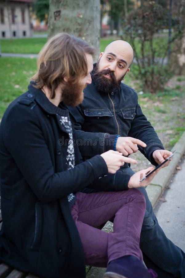Bärtiger moderner Mann zwei, der an Tablette arbeitet lizenzfreies stockbild