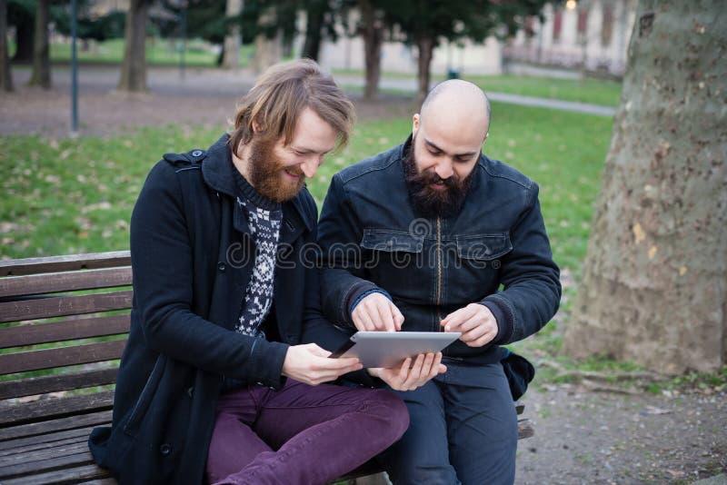 Bärtiger moderner Mann zwei, der an Tablette arbeitet lizenzfreie stockbilder