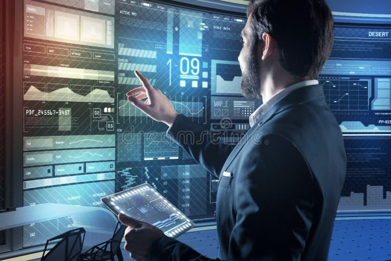 Bärtiger Programmierer, der auf seinen Computer beim Halten eines transparenten Gerätes zeigt stockfotos