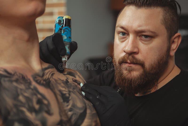 Bärtiger Tattooist, der Tätowierungen auf Körper seines Kunden macht lizenzfreie stockfotos