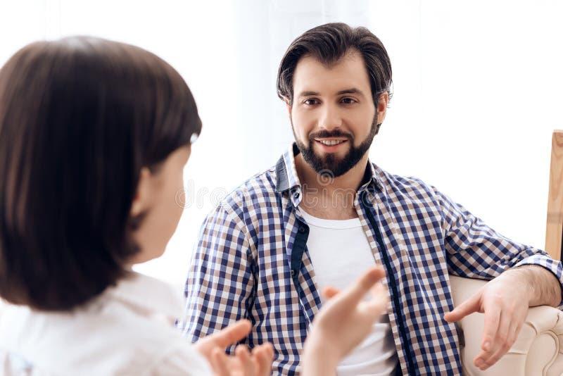 Bärtiger Vater hört aufmerksam auf jugendlichen Sohn zu Hause lizenzfreie stockbilder