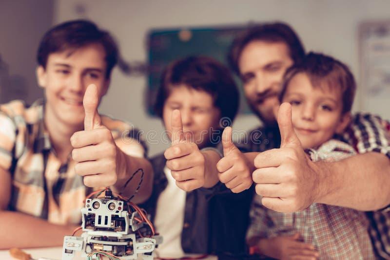 Bärtiger Vater und Söhne, die zu Hause Roboter konstruieren lizenzfreie stockfotografie