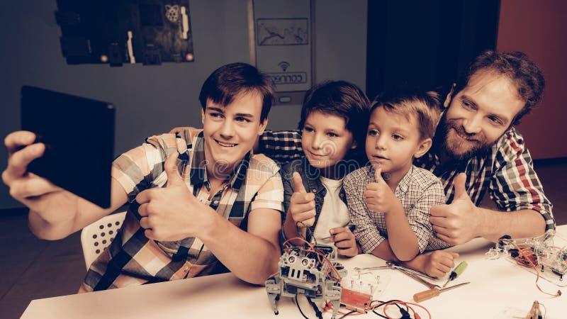 Bärtiger Vater und Söhne, die zu Hause Roboter konstruieren stockbild