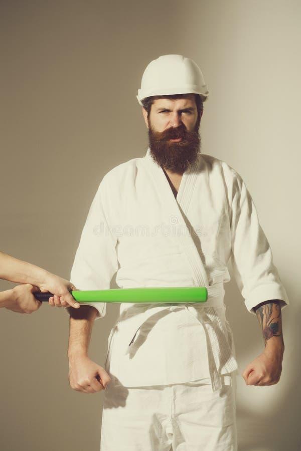 Bärtiger verärgerter Karatemann im Kimono, Sturzhelm mit Baseballschläger stockfoto