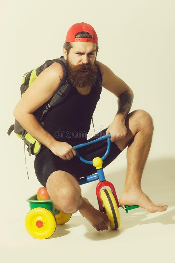 bärtiger verärgerter Mann mit Tasche, Apfel auf Fahrradspielzeug stockfoto