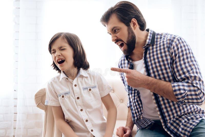 Bärtiger verärgerter Vater schilt schreienden Sohn lizenzfreie stockfotos