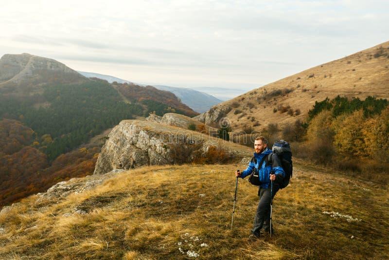 Bärtiger Wanderer der Rothaarigen, der oben der Hinterweg genießt Landschaft geht Wanderermannklettern mountans mit Wanderstöcken stockfotografie