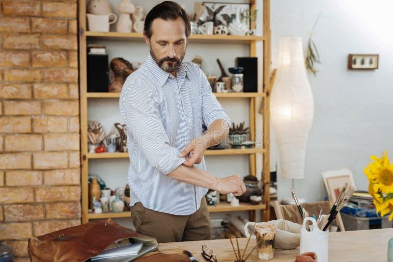 Bärtiges dunkelhaariges handicraftsman, das in seiner neuen Werkstatt steht lizenzfreies stockbild