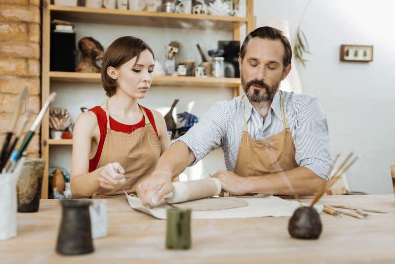 Bärtiges dunkelhaariges handicraftsman, das Vorlagenklasse für Frau gibt lizenzfreie stockfotos