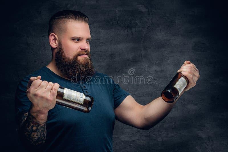 Bärtiges männliches, zwei leere Bierflaschen betrachtend lizenzfreie stockfotografie